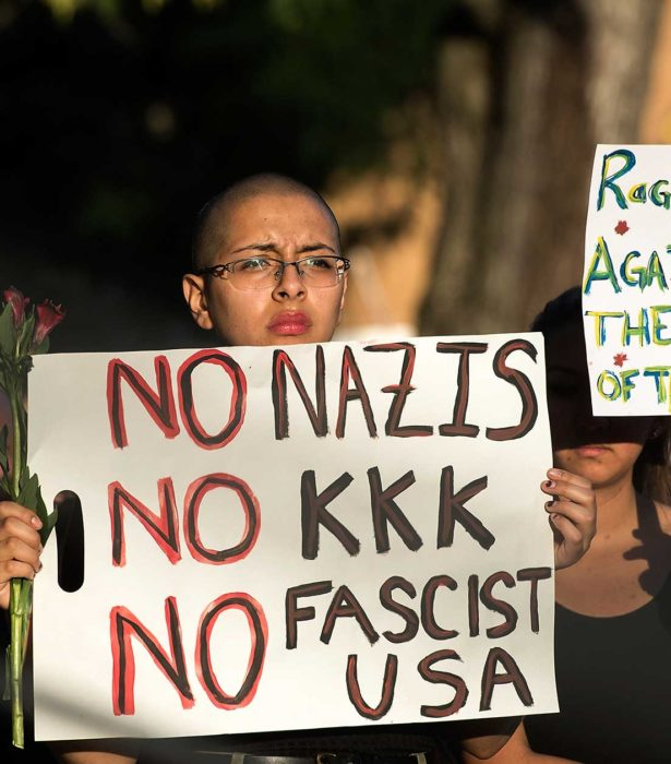 Brenda Diaz-Castro, holds a sign during a candlelight vigil on Sunday, Aug. 13, 2017, in Harrisonburg, Va. The vigil was held for the victims of the violence in Charlottesville, Va., on Saturday.