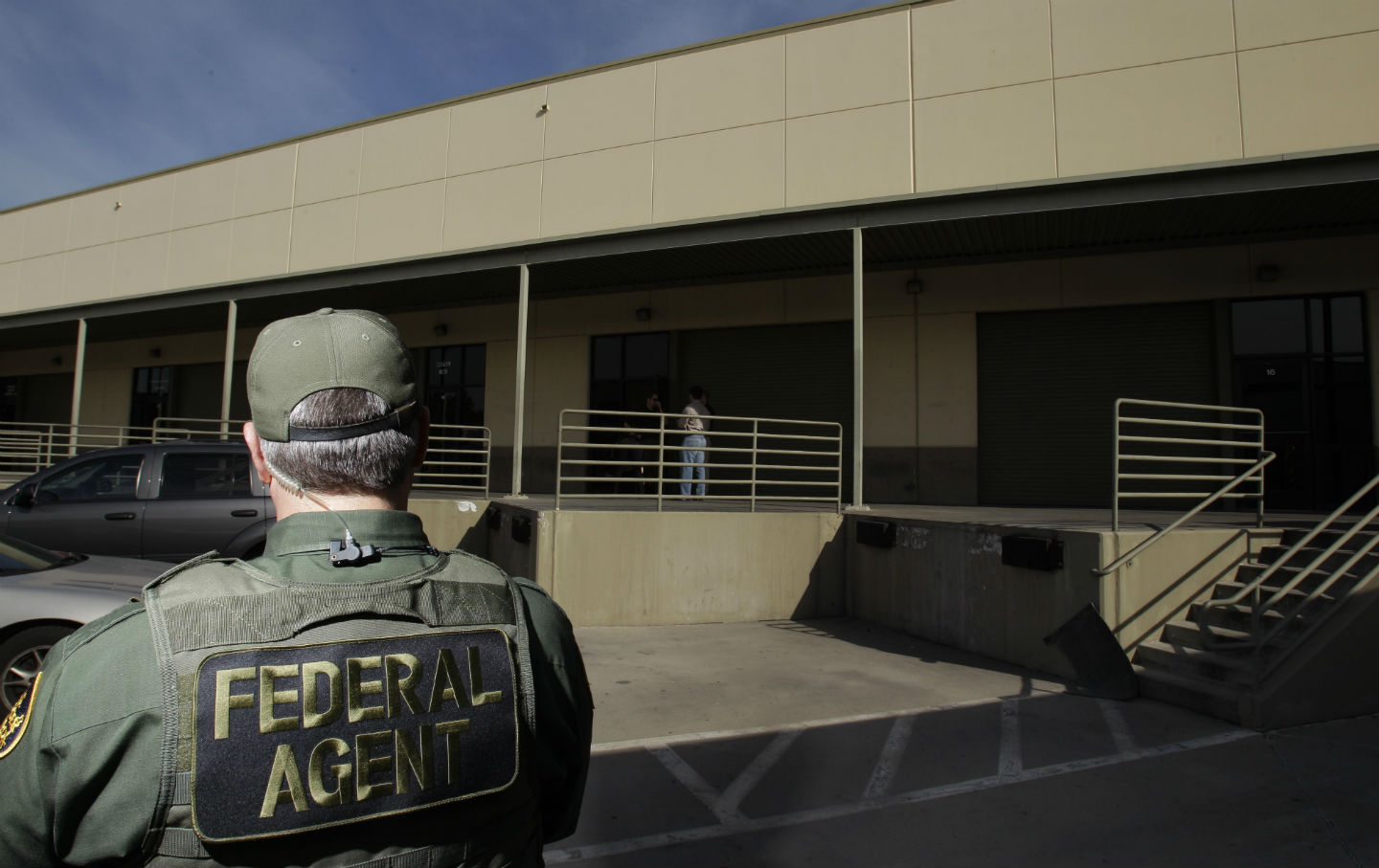 A federal agent stands outside of a building in San Diego, CA.