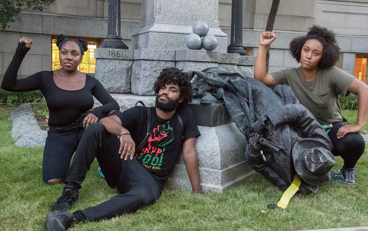 Activists pose after a Confederate statue is toppled in Durham, NC.