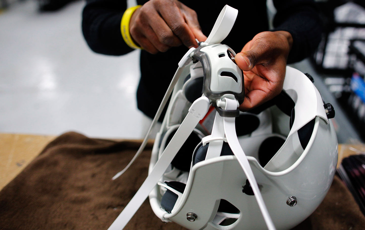 A worker assembles a football helmet in Lowell, Massachusetts.