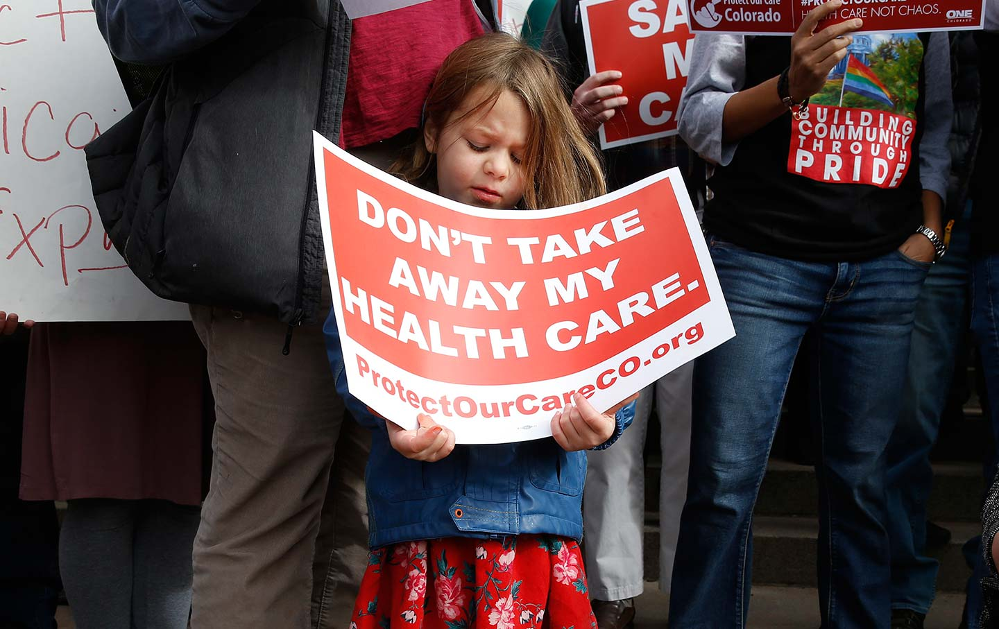 A girl stands holding a sign alongside supporters of the Affordable Care Act at a rally in Denver on Tuesday, January 31, 2017.