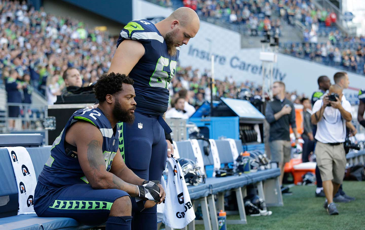 Michael Bennett sits during the national anthem.