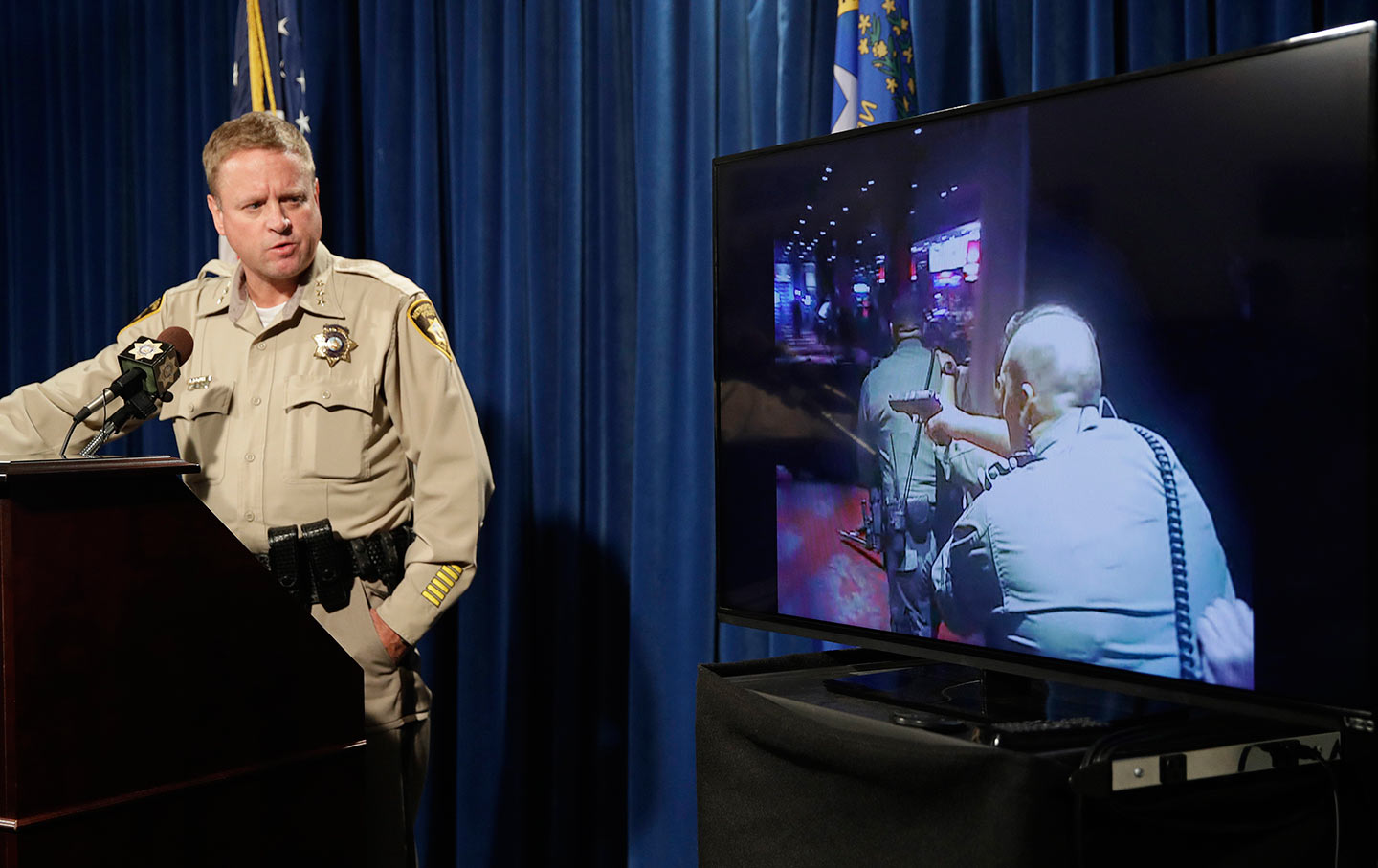 Las Vegas police Undersheriff Kevin McMahill watches body camera footage during a press conference