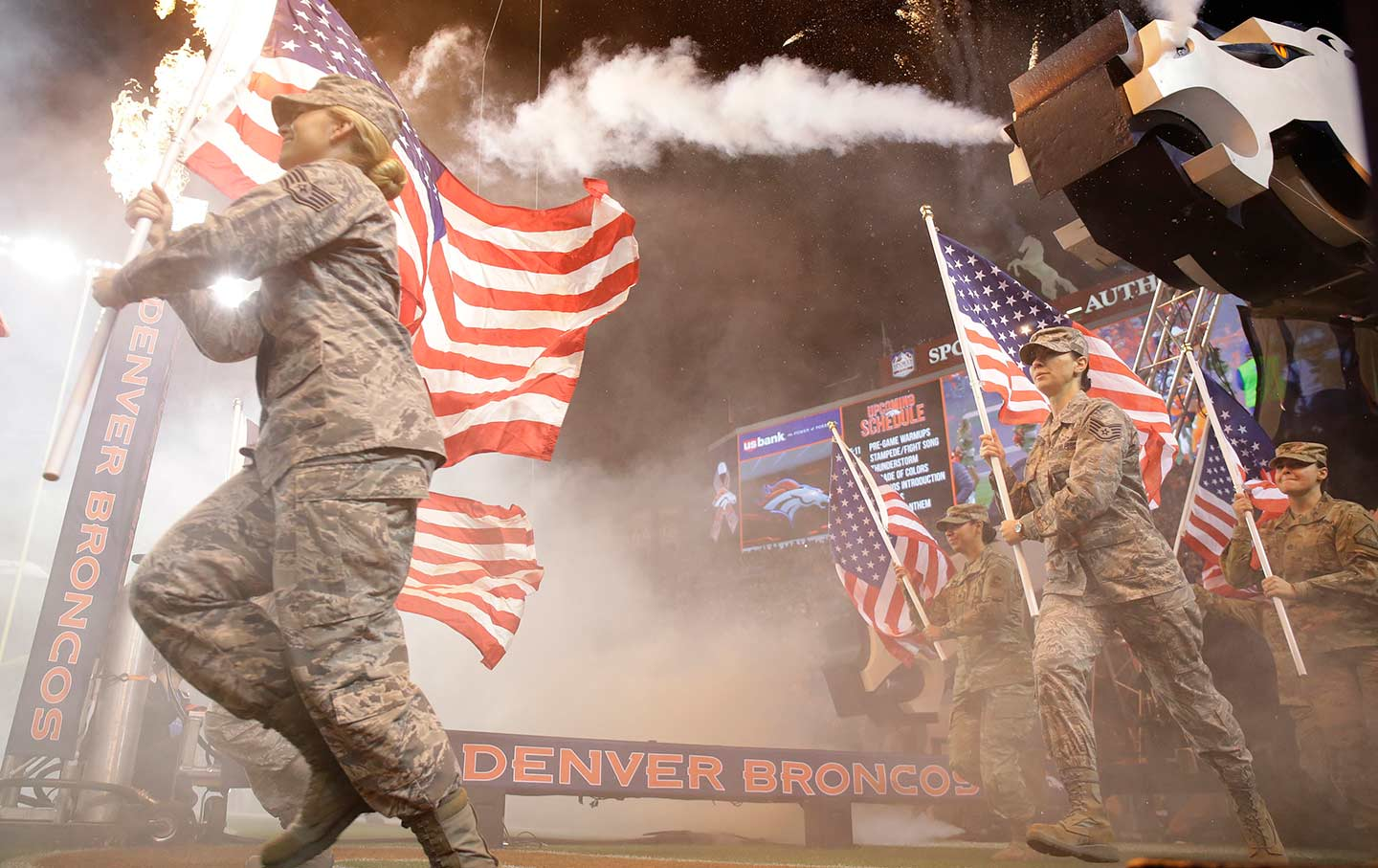Military personnel carry flags