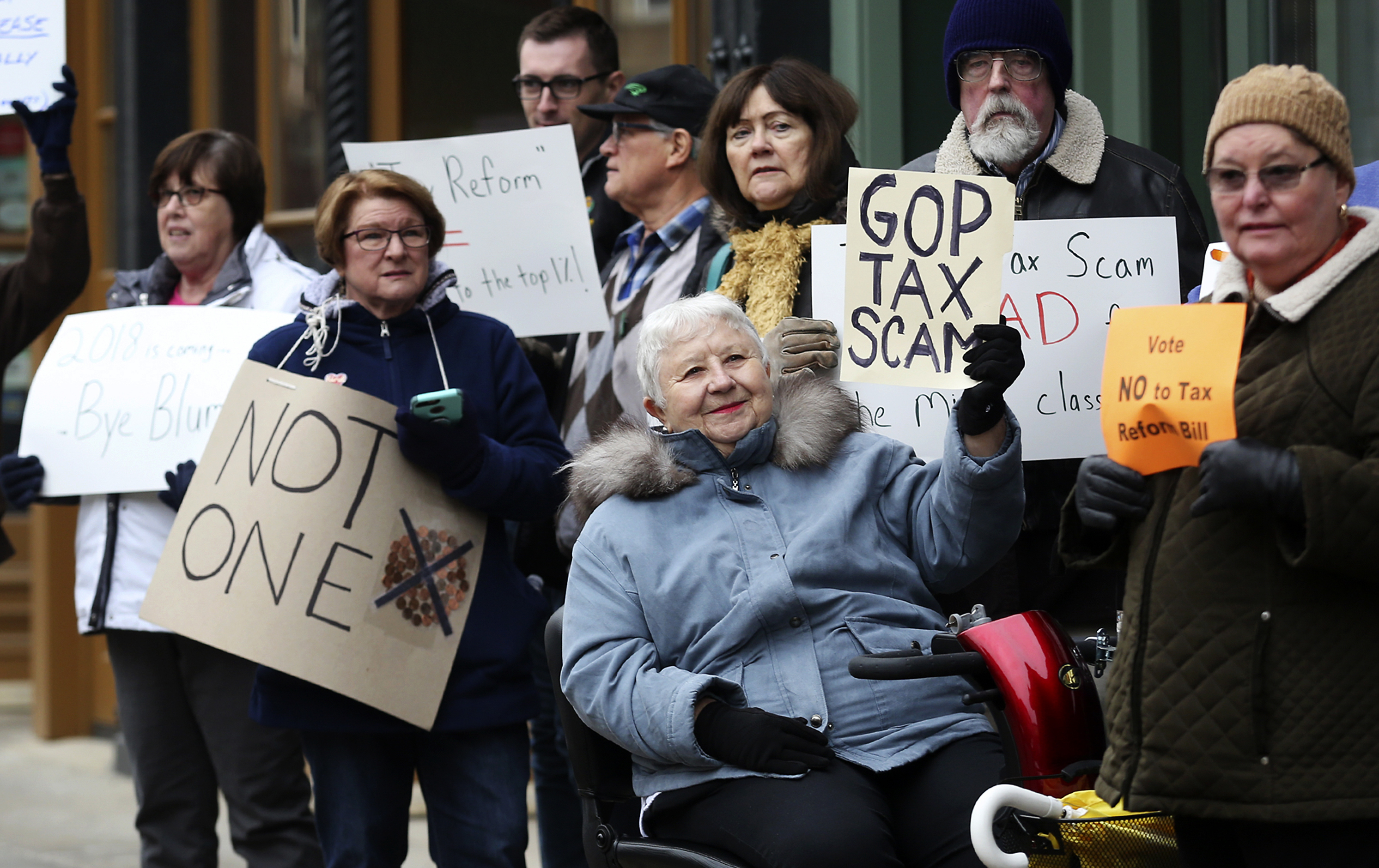 Marilyn Schroeder, center, gathers with other protesters to oppose the Republican tax plan.