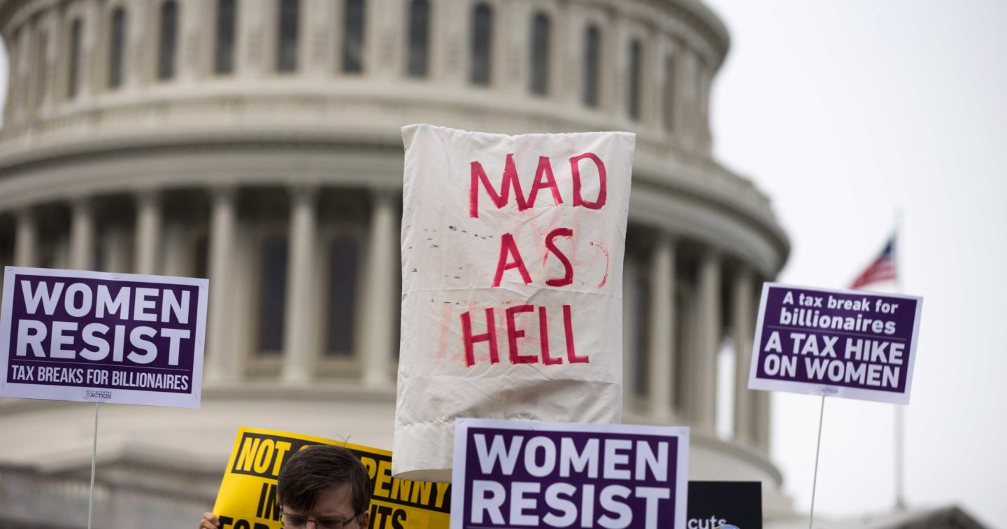 Demonstrators hold up protest signs in front of the United States Capitol