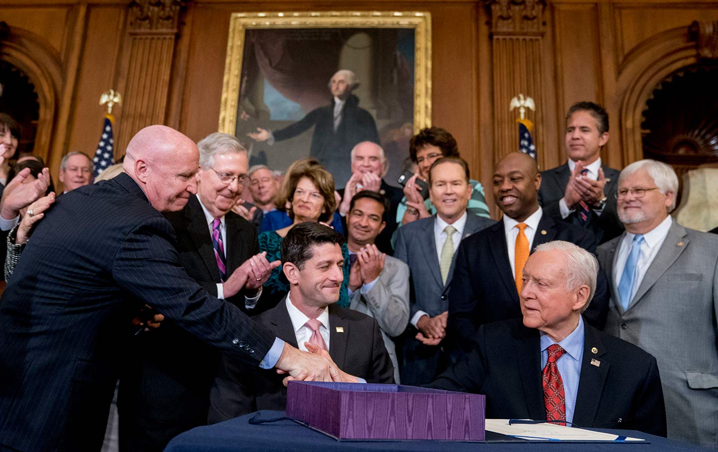Congressmen celebrate after House Speaker Paul Ryan and Senate Finance Committee Chairman Orrin Hatch sign the final version of the GOP tax bill on December 21, 2017