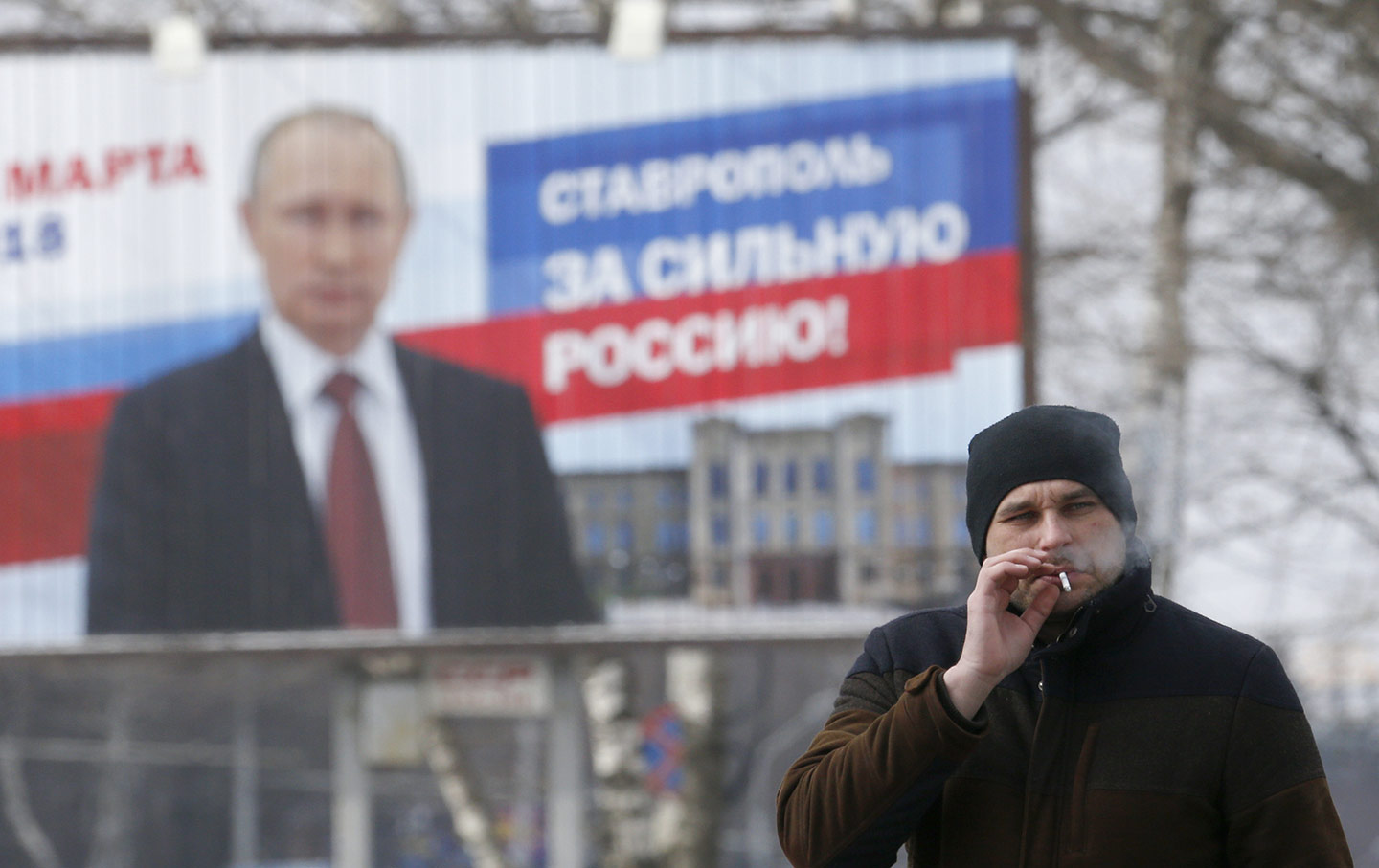 Man smokes in front of Putin billboard