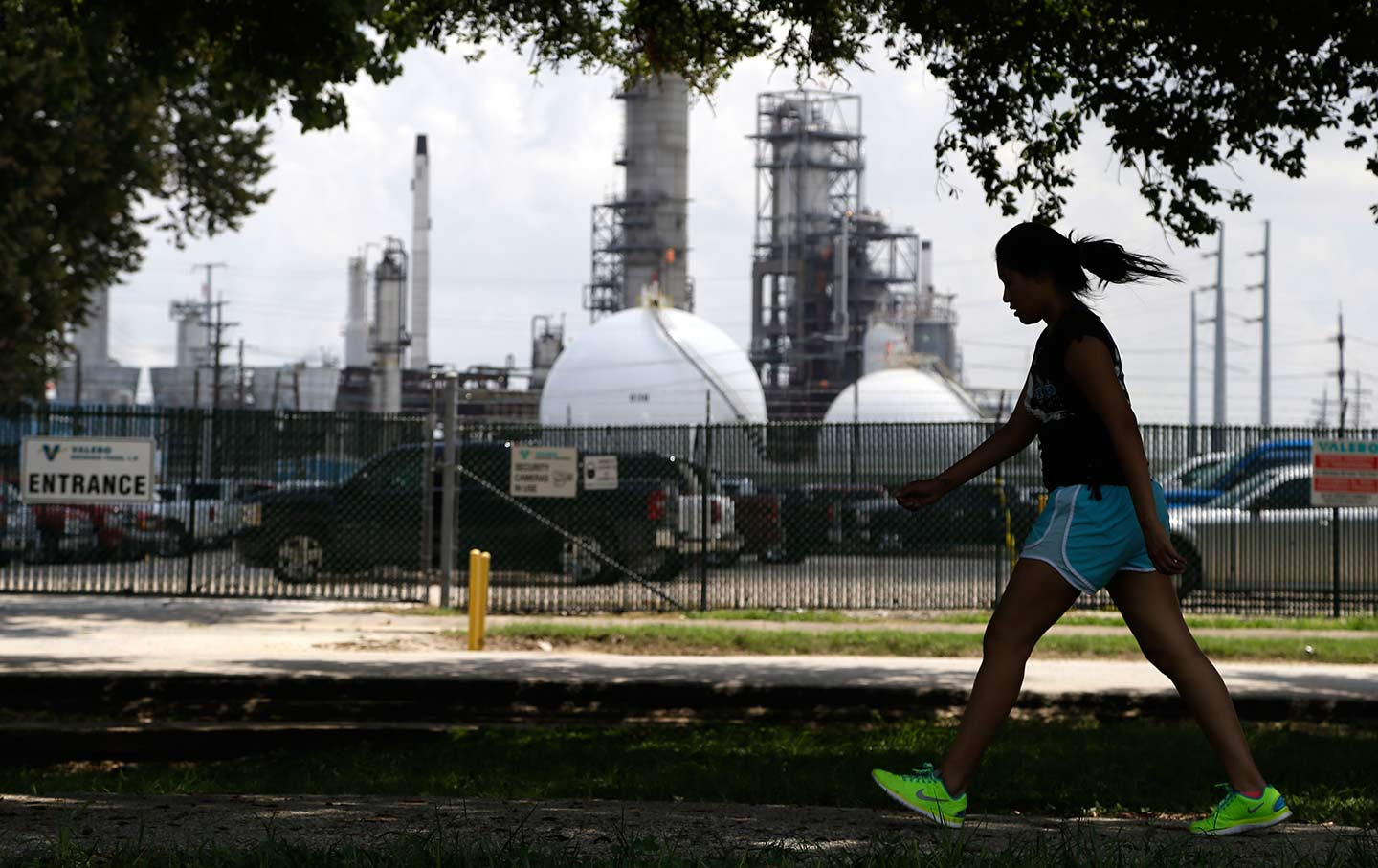 Girl walks past Houston oil refinery