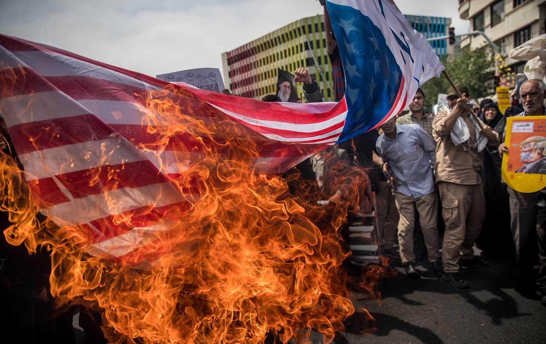 Iranian protesters burn US flag