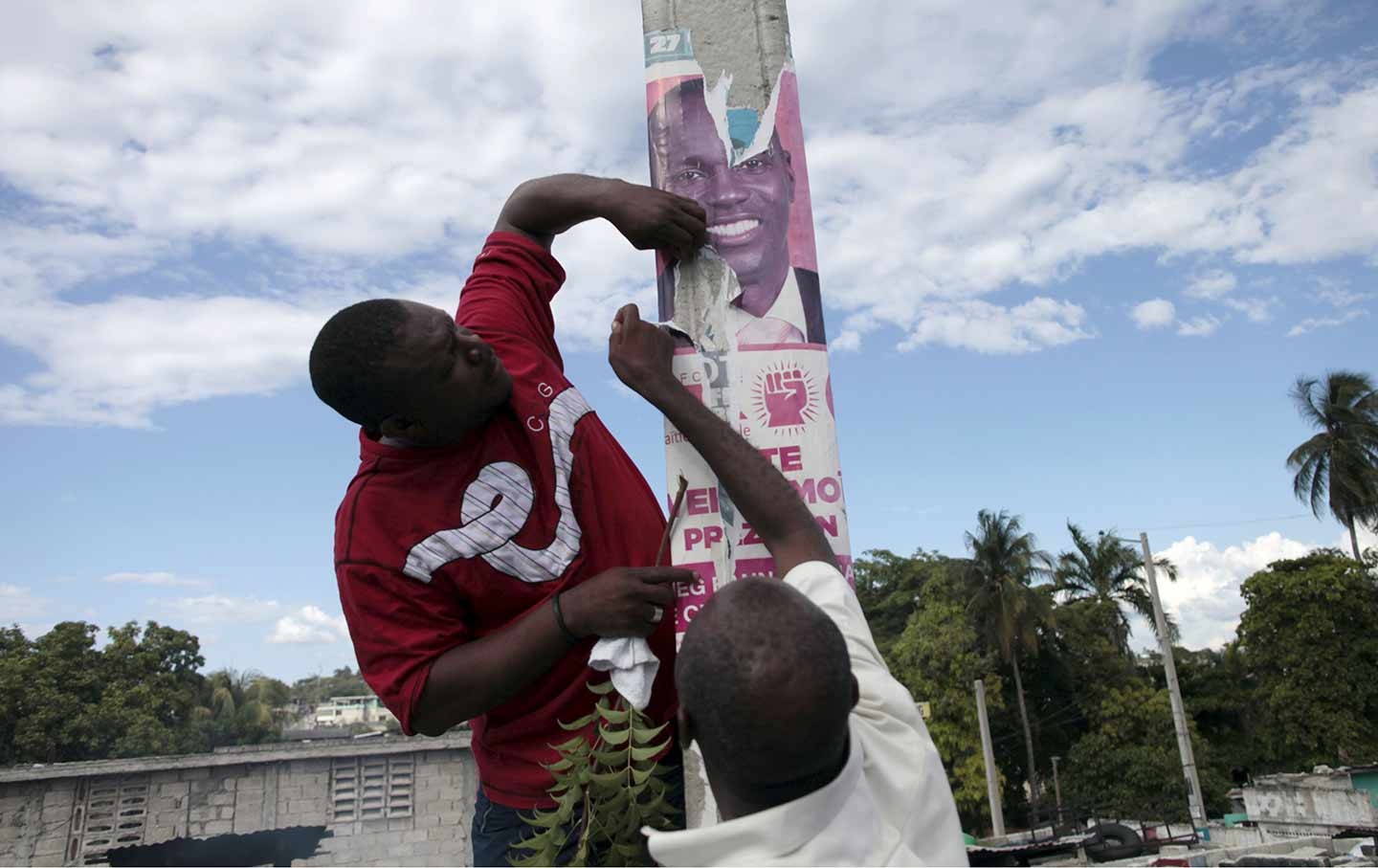 Protesters rip an electoral poster of president Jovenel Moïse