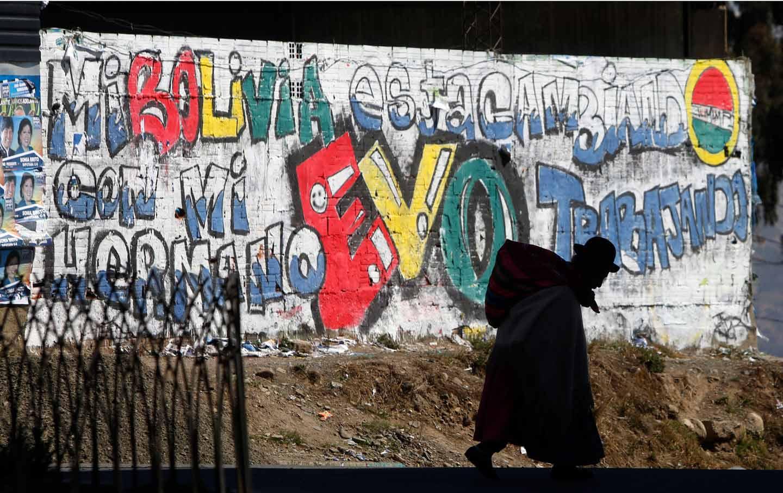 Elderly woman walks past a mural celebrating Bolivian president Evo Morales