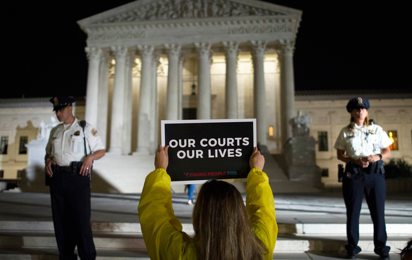 A demonstrator protests in front of the Supreme Court as President Donald Trump announces Judge Brett Kavanaugh as his Supreme Court nominee.