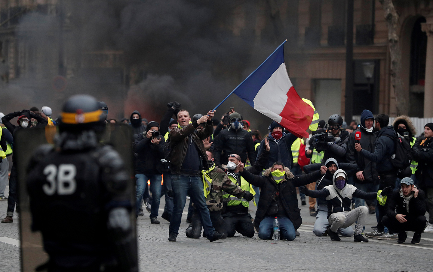 A protester waves a French flag during clashes with police at a demonstration by the