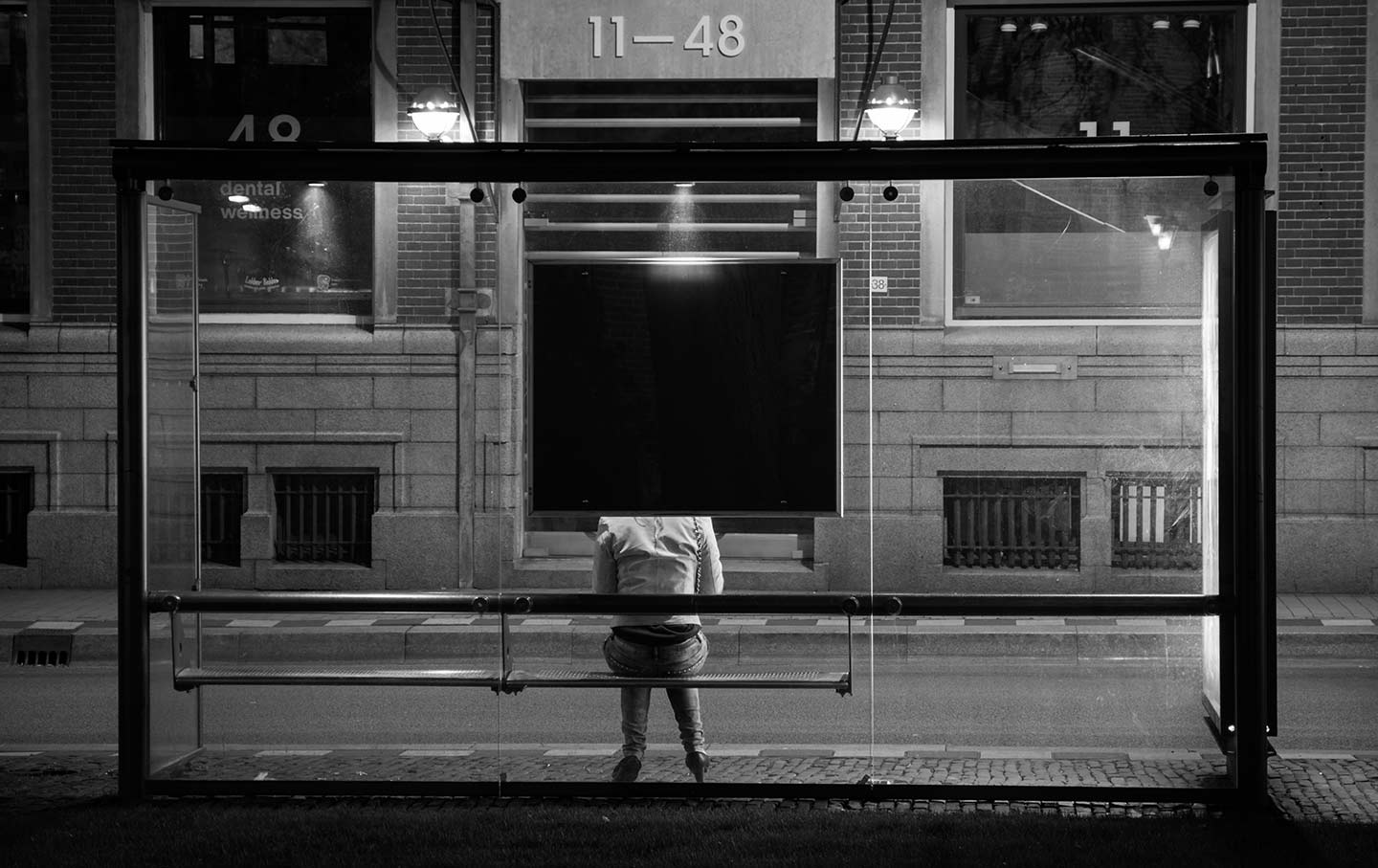 Woman at lonely bus stop.