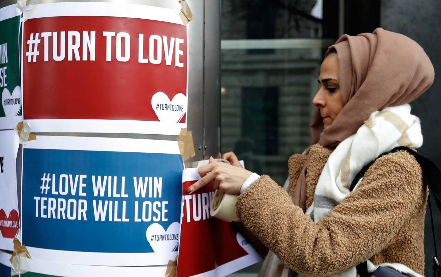 A demonstrator hangs banners from multi-faith group 'Turn to Love'