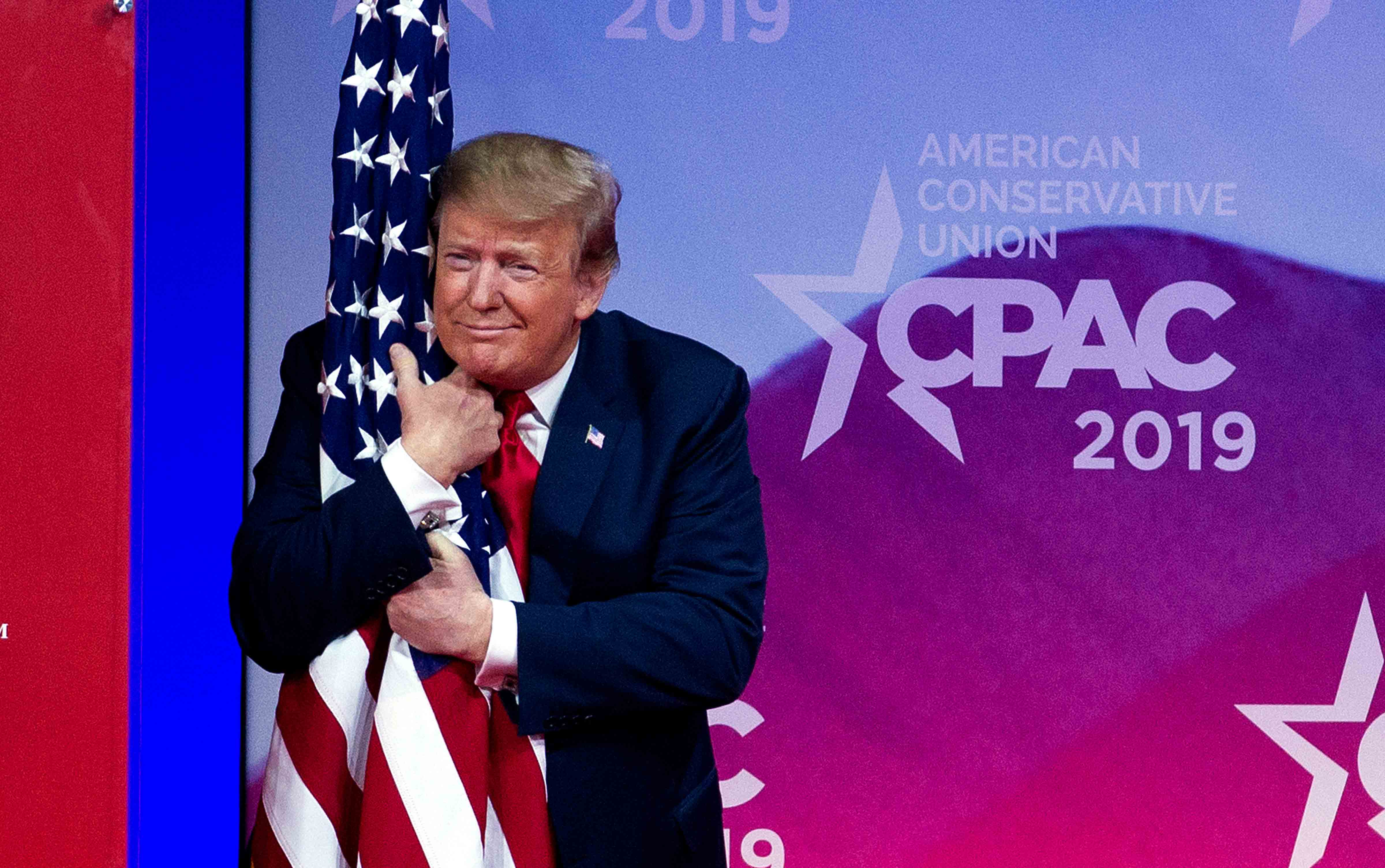 Trump hugs American flag
