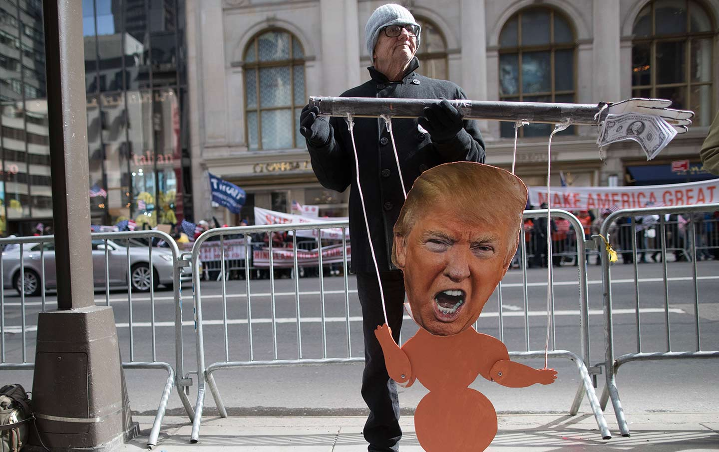 A Protester holds a Trump puppet