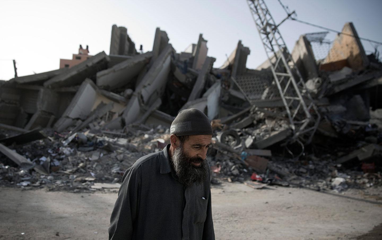 Eldery man walks by destroyed Gaza building