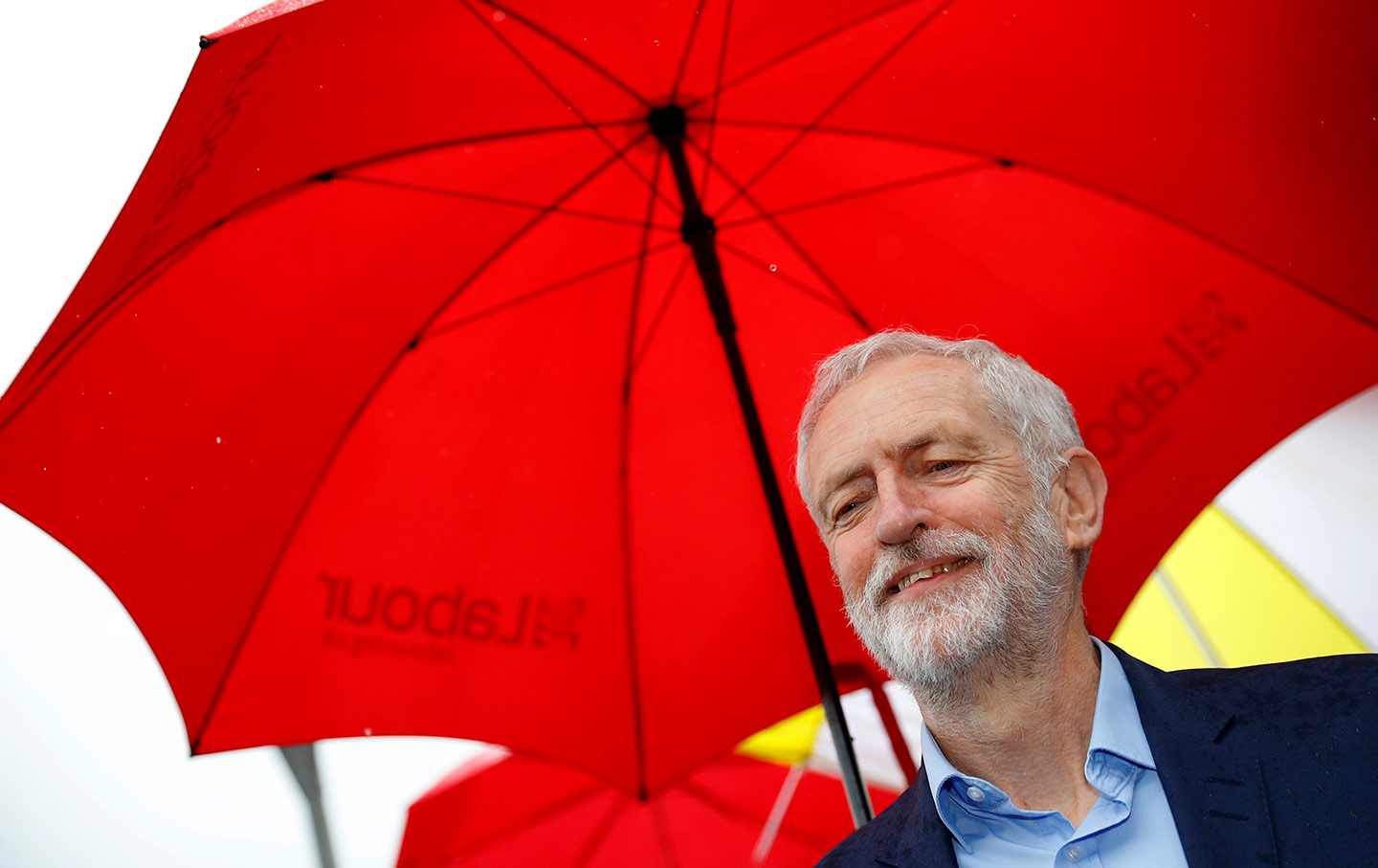 Jeremy Corbyn under a red umbrella.