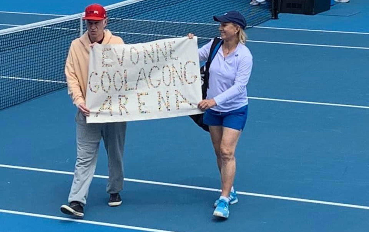 John McEnroe and Martina Navratilova walk onto the court at the Australian Open with a banner that reads