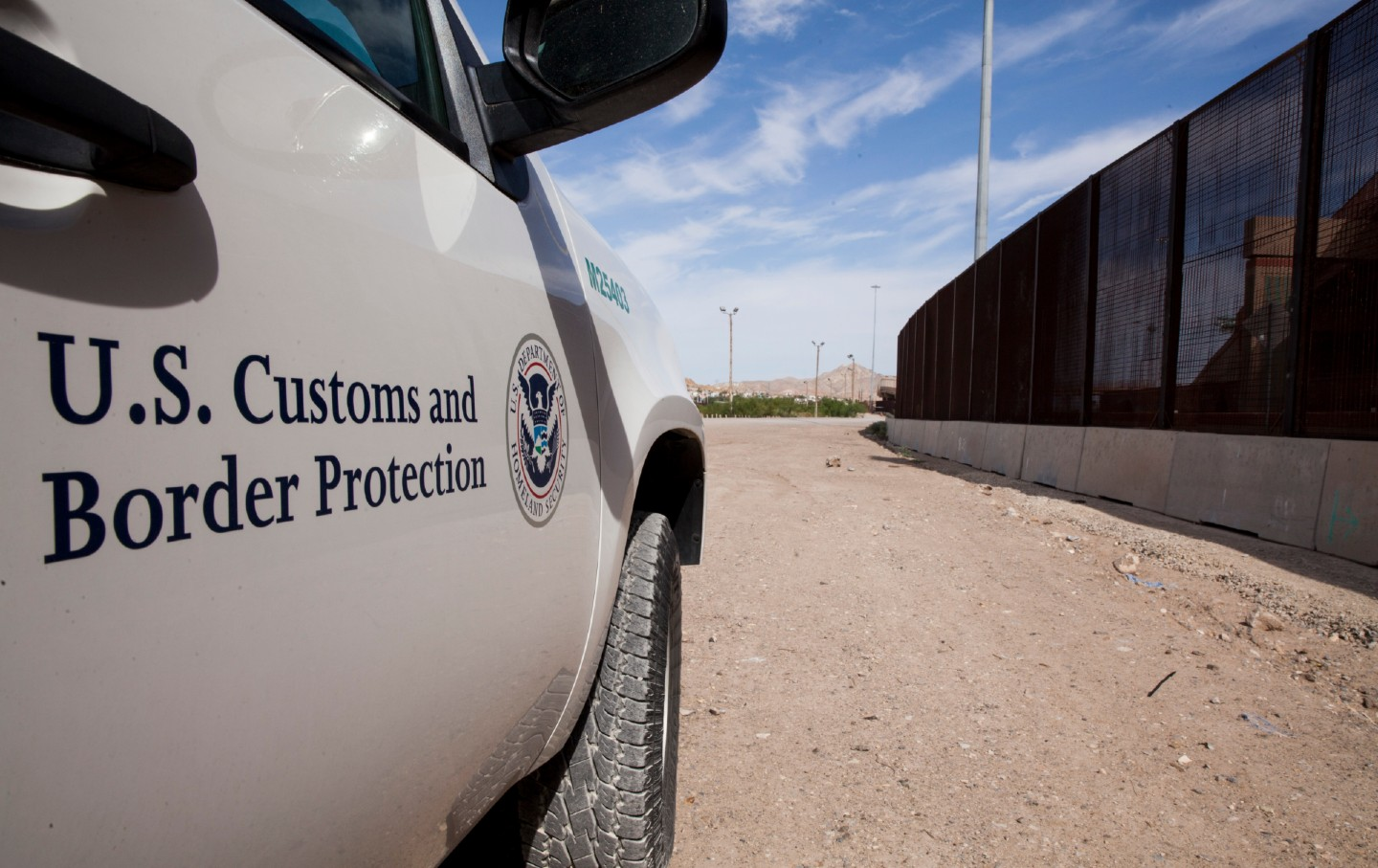 A Customs and Border Patrol car near the border fence.