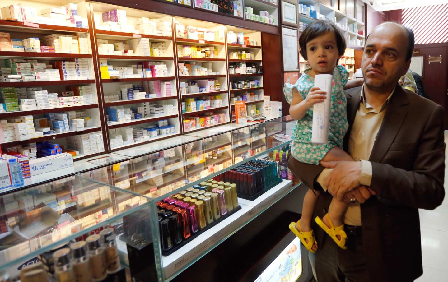 An Iranian man and child in a drugstore, 2018