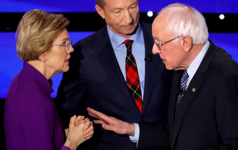 Senator Warren speaks with Senator Sanders.