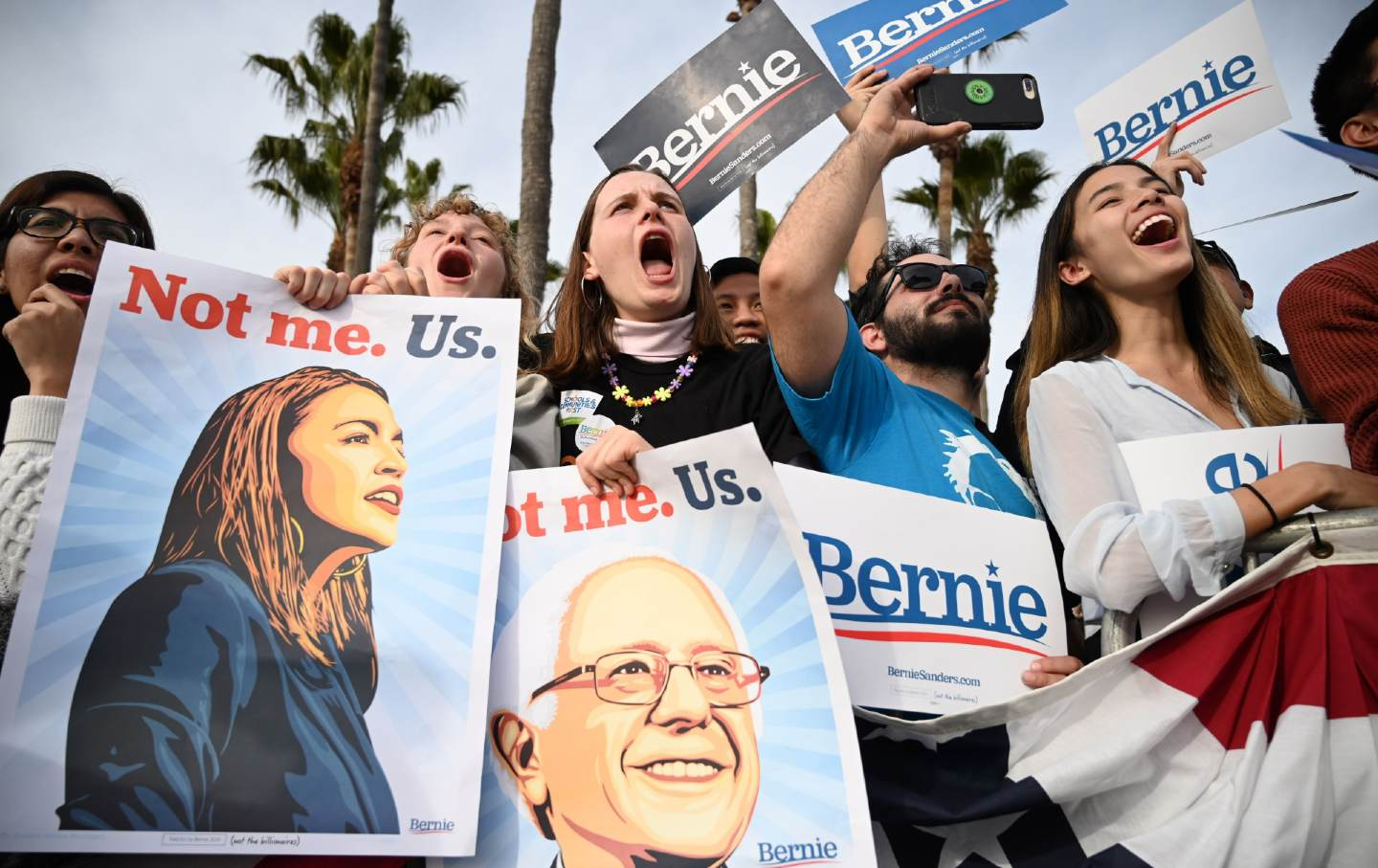 Bernie supporters at a rally, holding posters.