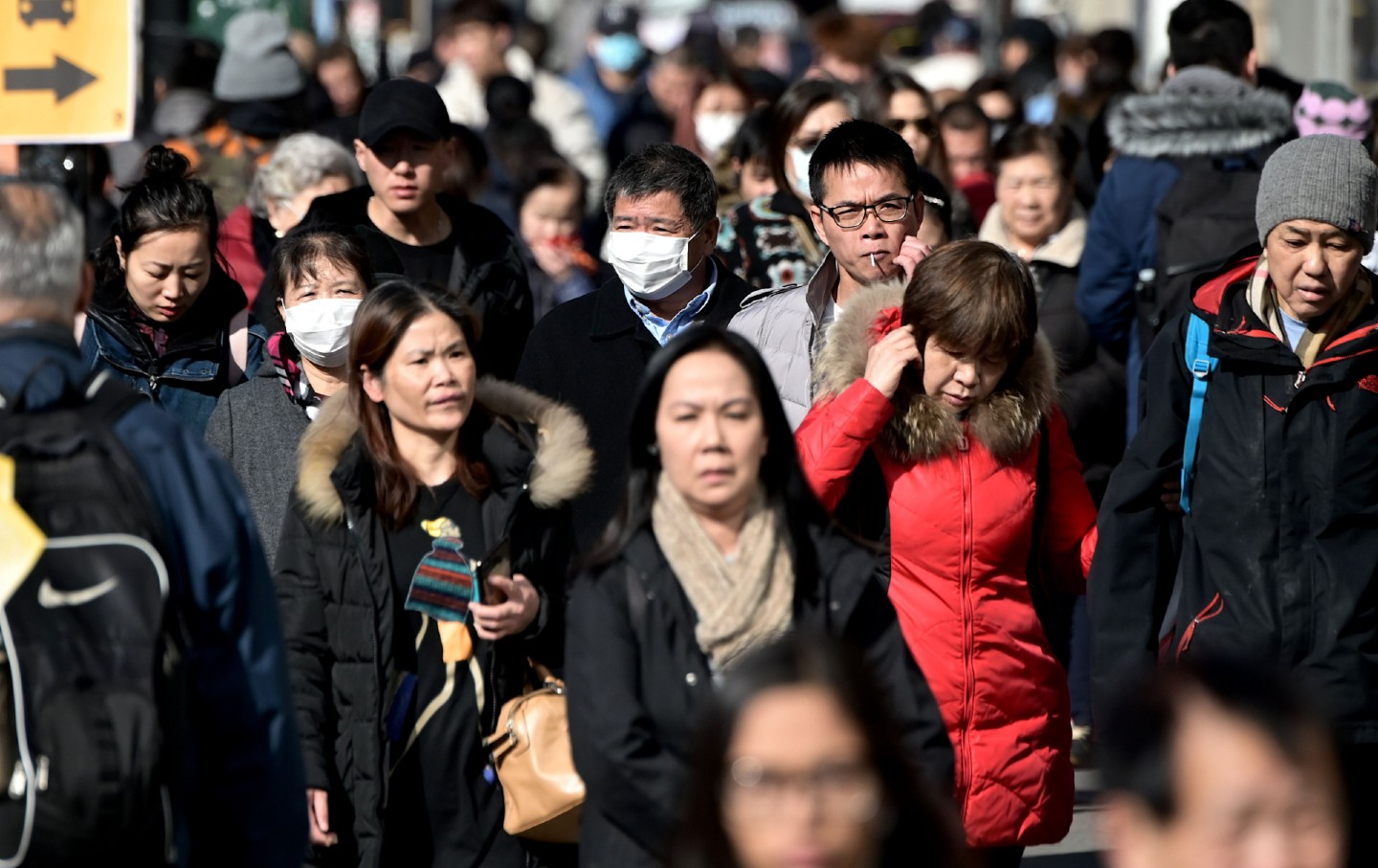 People in surgical masks in Flushing, Queens, New York City.