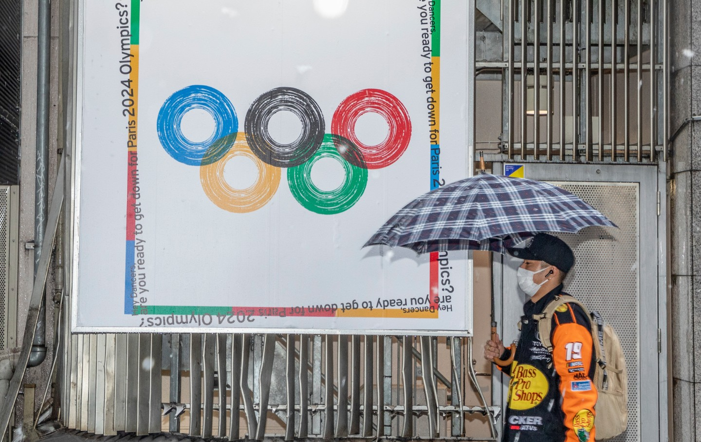 A man in a mask walks by an Olympic 2024 poster