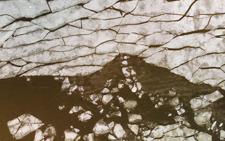 Aerial of broken ice in Helsinki bay melting into brown water.