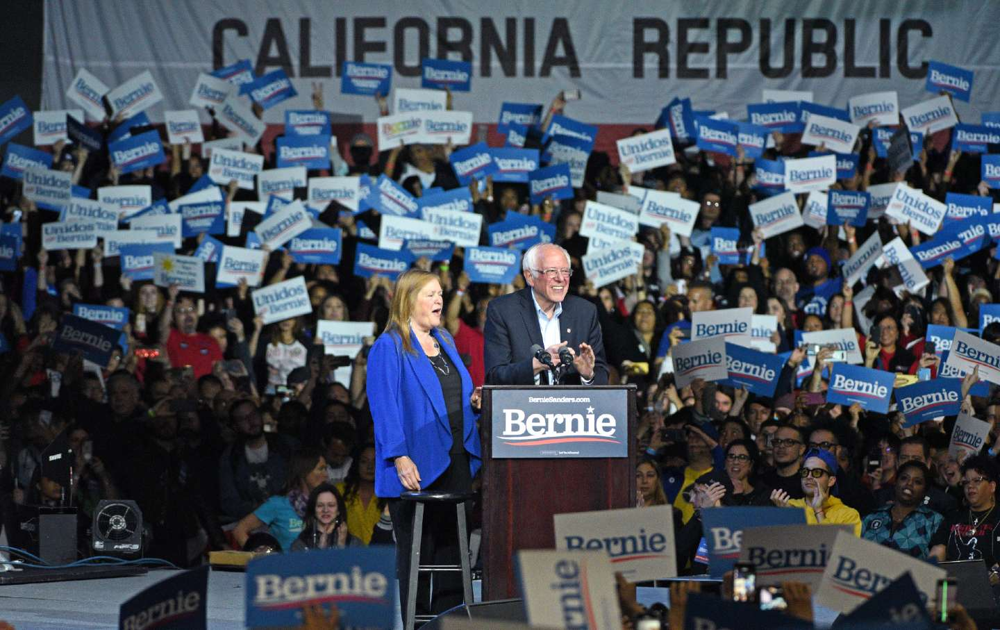 Jane and Bernie Sanders speaking to a large crowd in California.