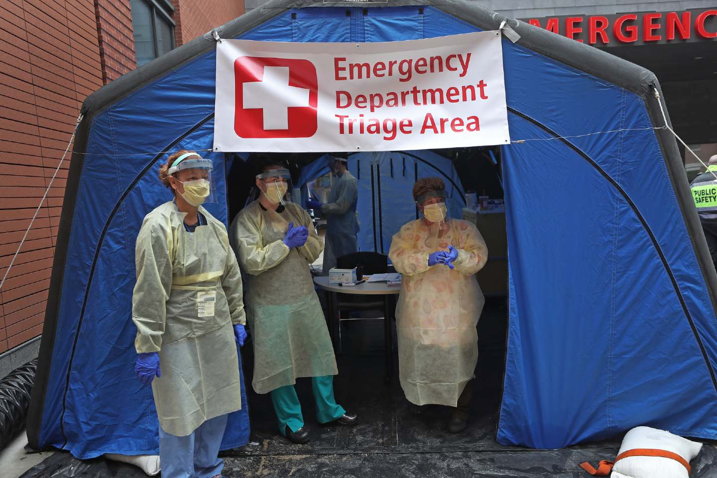 Nurses in protective gear stand outside a tent labelled