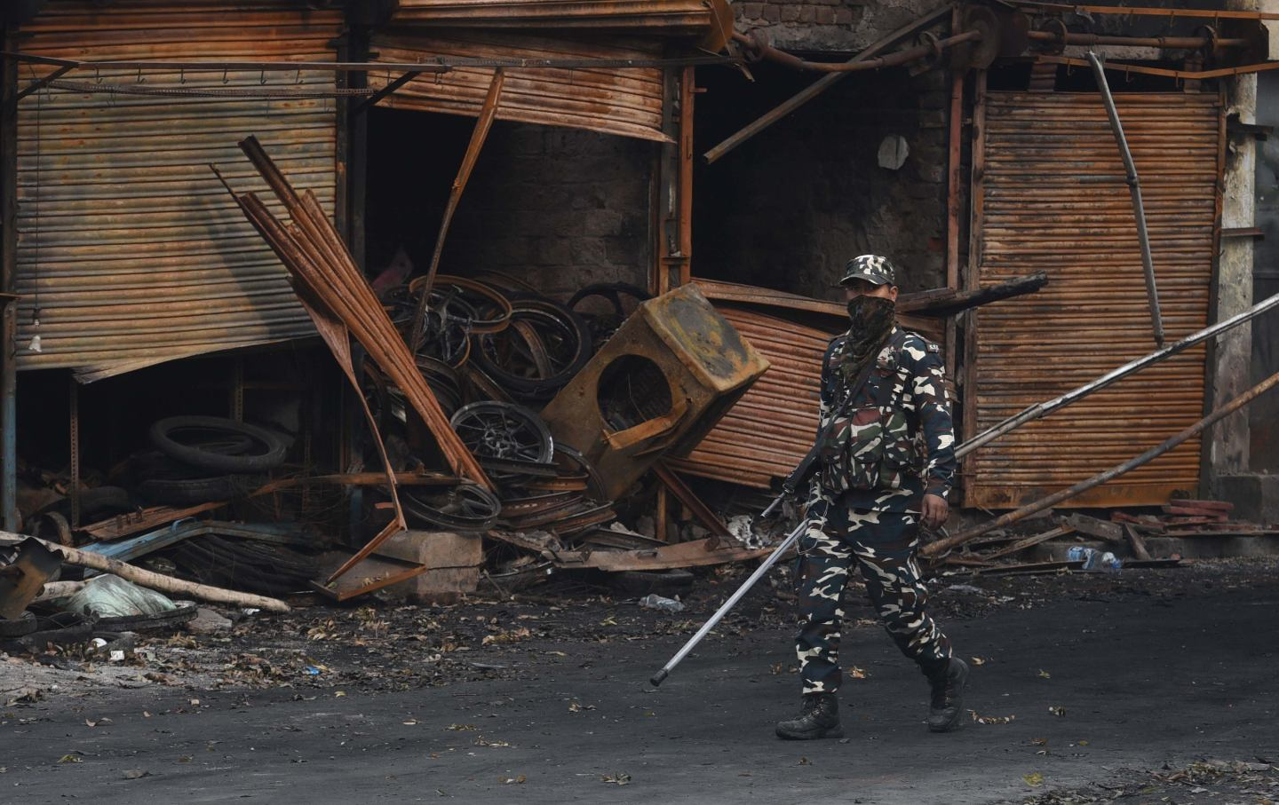 Sashastra Seema Bal personnel walk past burnt and damaged shops