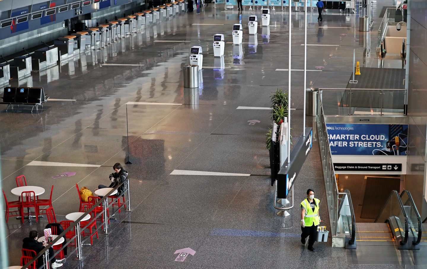 A cleaner walks though Logan airport