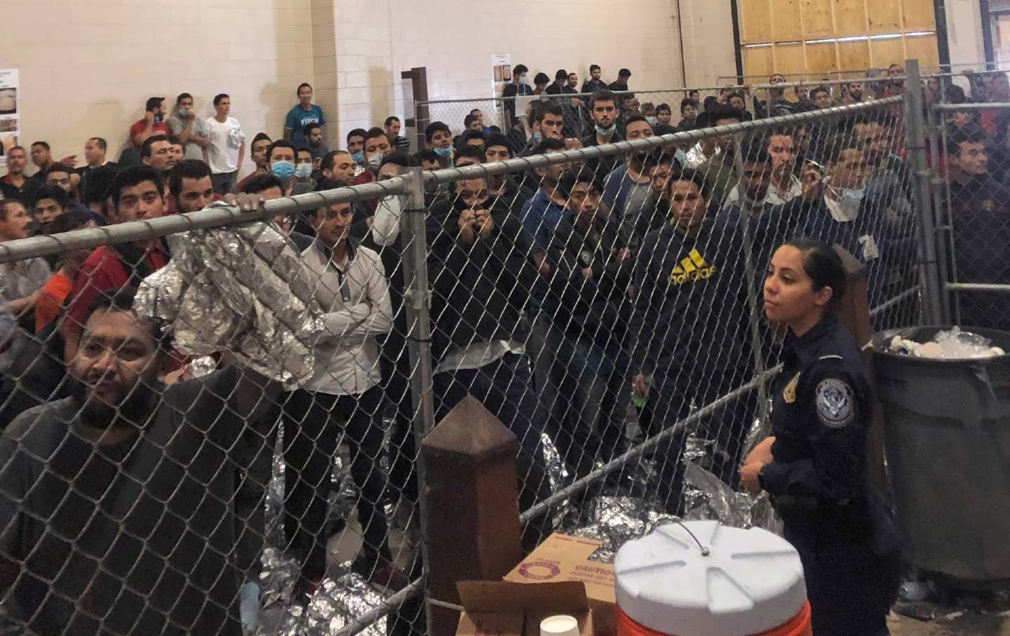 A crowded detention center with migrants looking in from behind a fence.