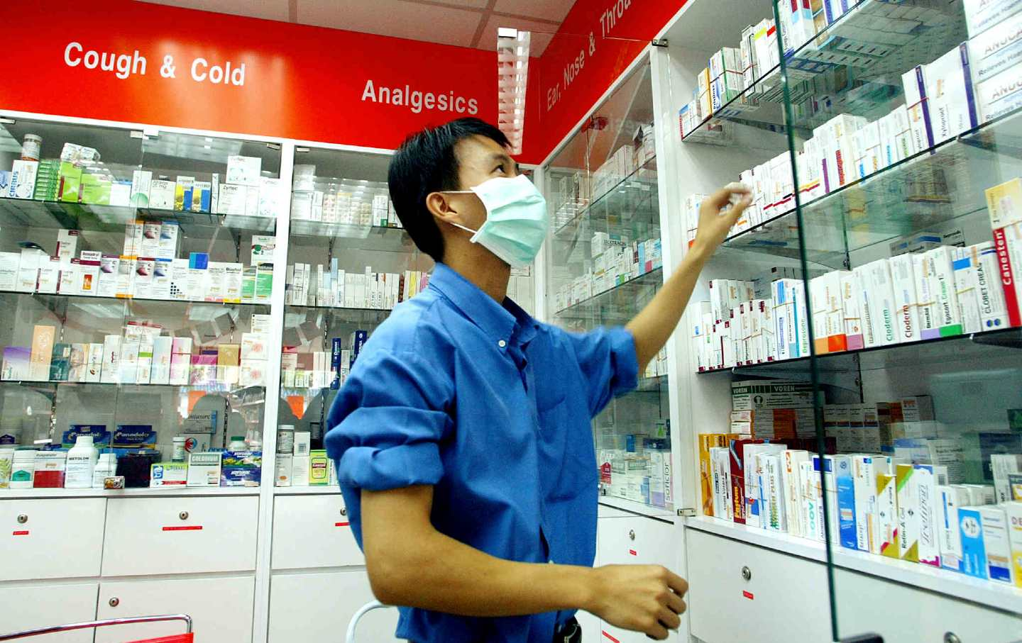 A pharmacist checks his stock while wearing a surgical mask.