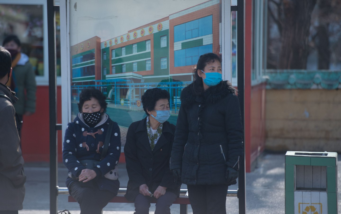 People in Pyongyang wait at a bus stop, wearing face masks.