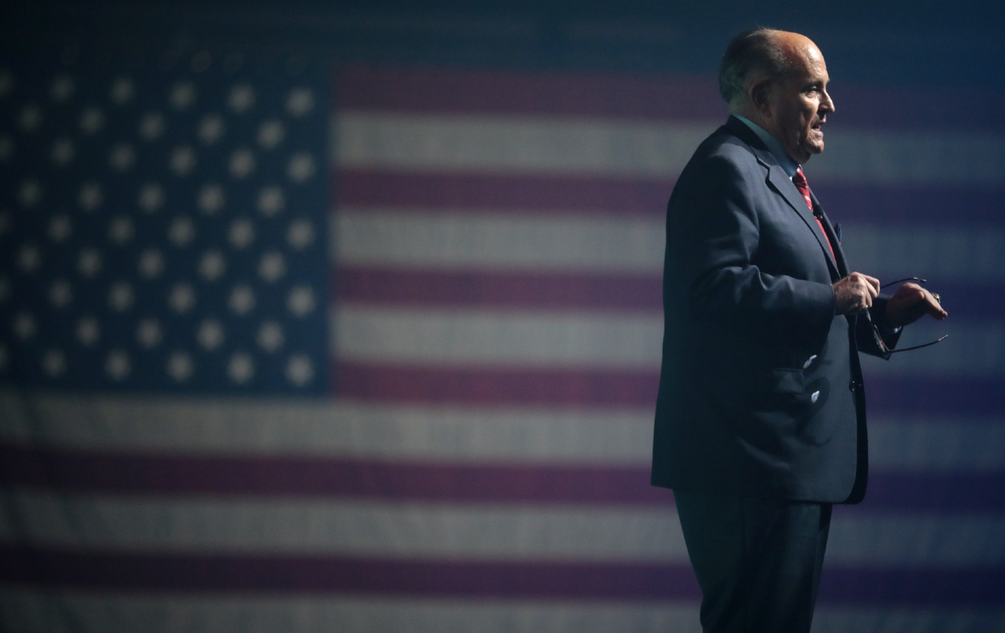 Rudy Giuliani standing and speaking in front of a US flag.