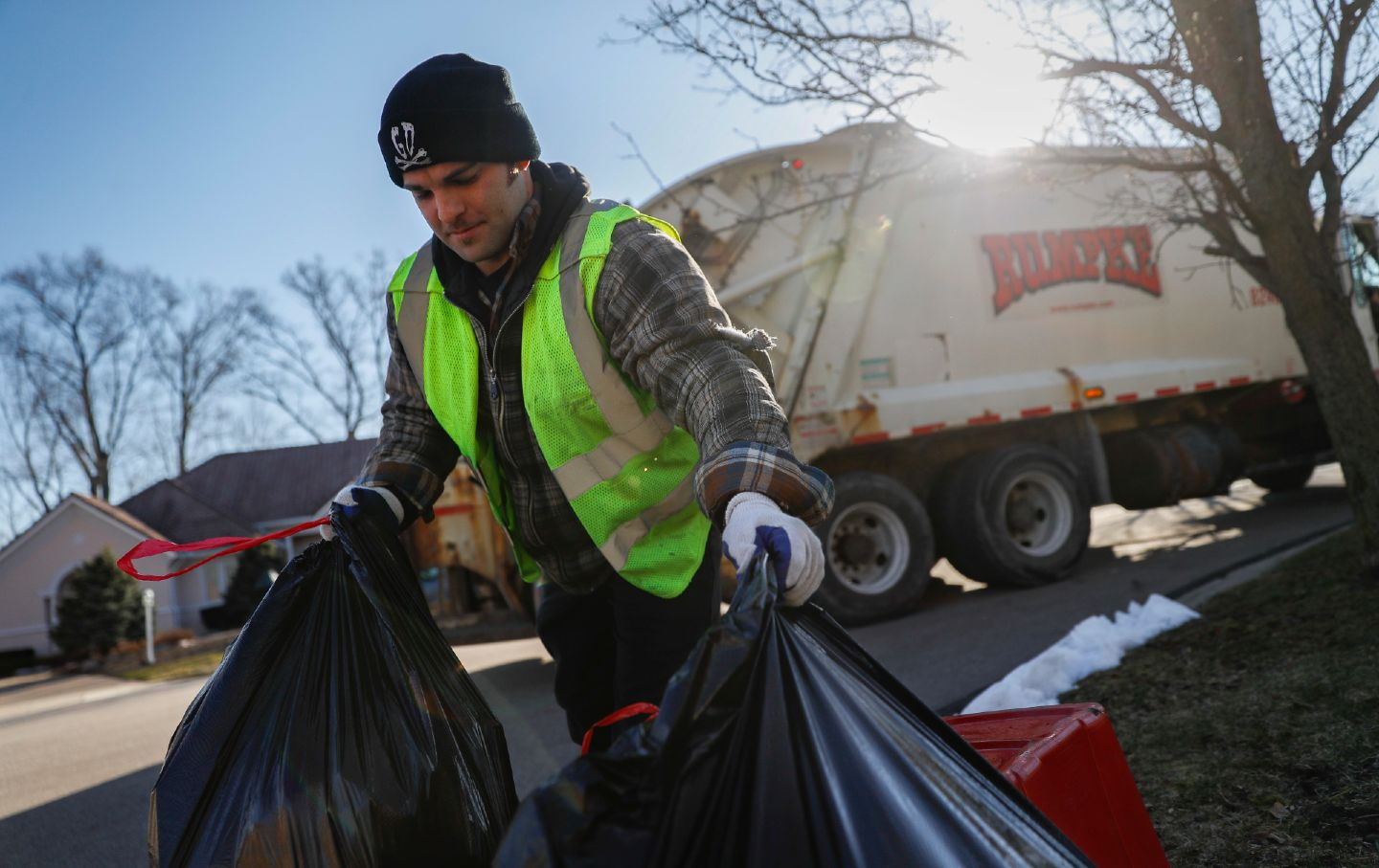 A sanitation worker hauls recycling bags in Beavercreek, Ohio.