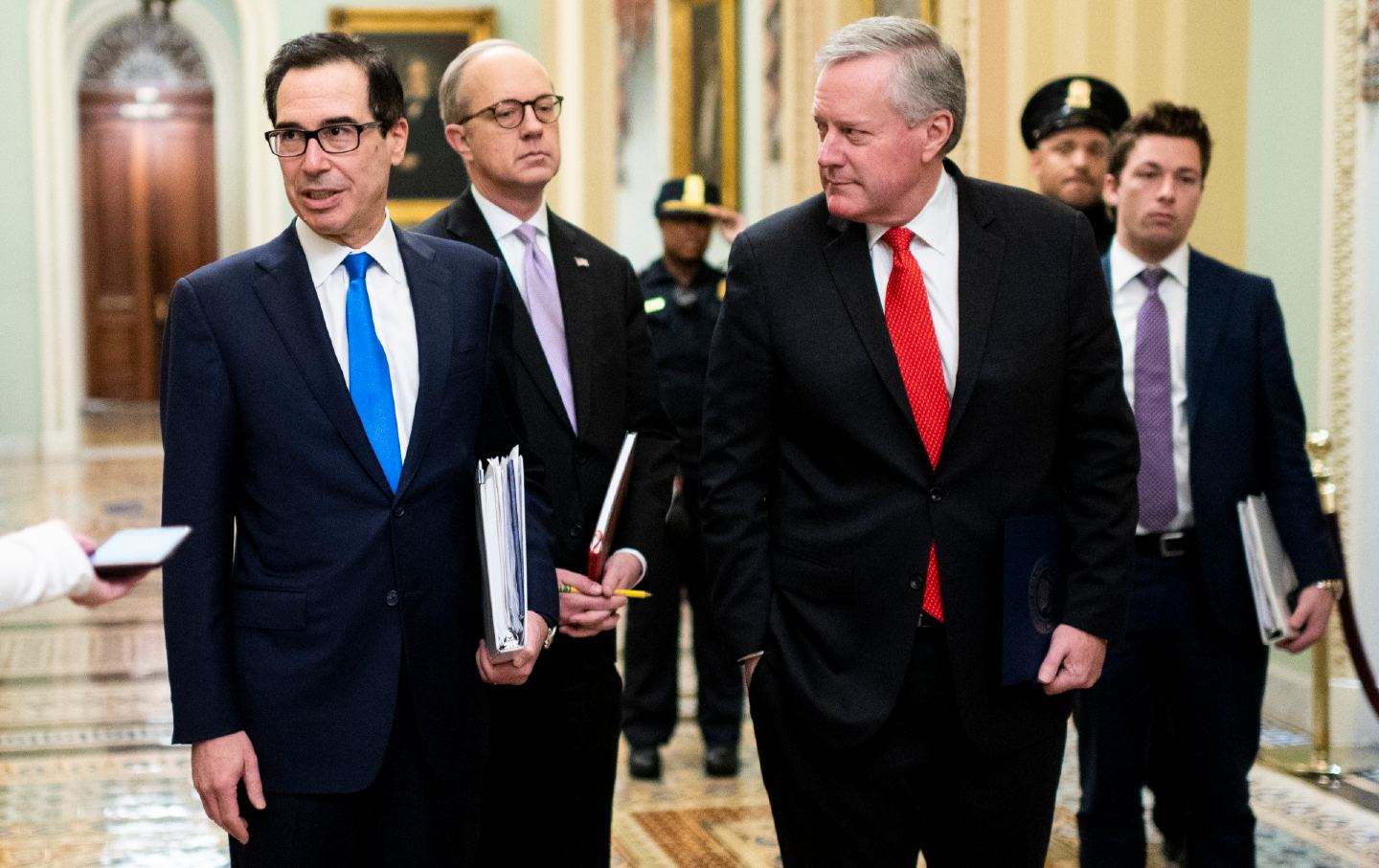 Three men in suits walk down a hallway of the Capitol building.
