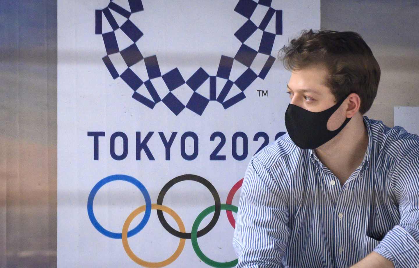 A man wearing a facemask sits in front of a Tokyo 2020 advertisement