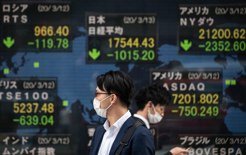 Two people walking past the Tokyo Stock Exchange.