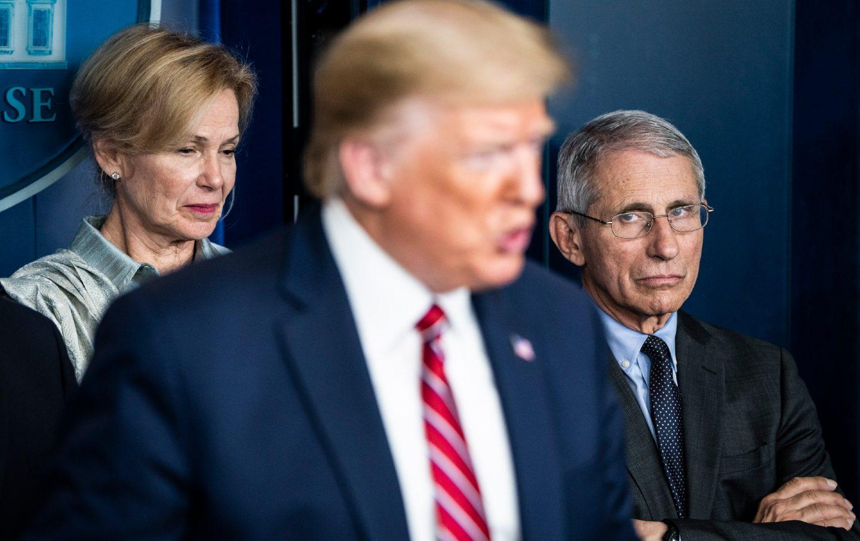Two figures stand behind Trump as he speaks.