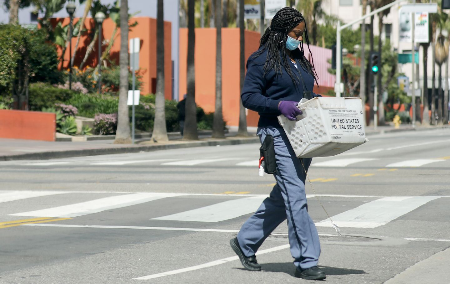 USPS worker with gloves and mask crosses street amid coronavirus outbreak in LA