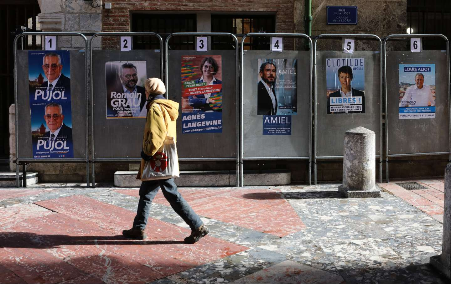 A woman walks by an posters in front of the city hall of Perpignan
