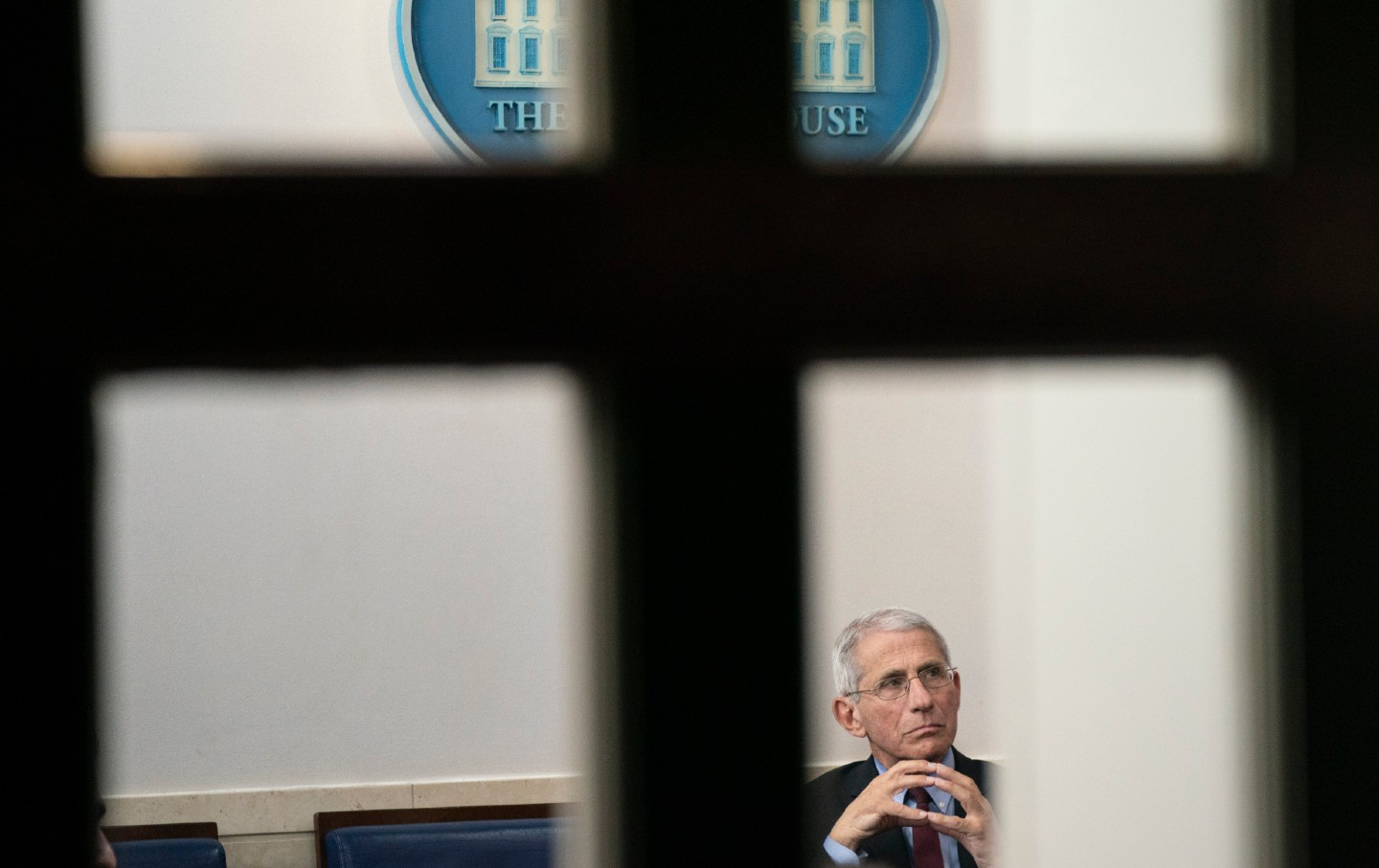 Dr. Anthony Fauci, pictured through a window, listens to a press briefing.