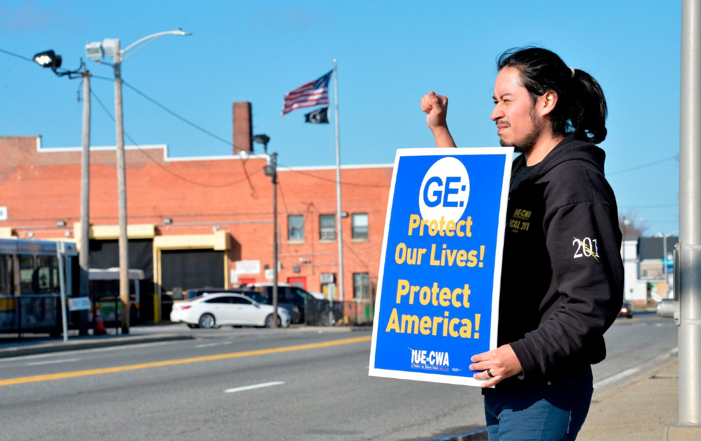 A GE worker stands outside the plant with a sign reading