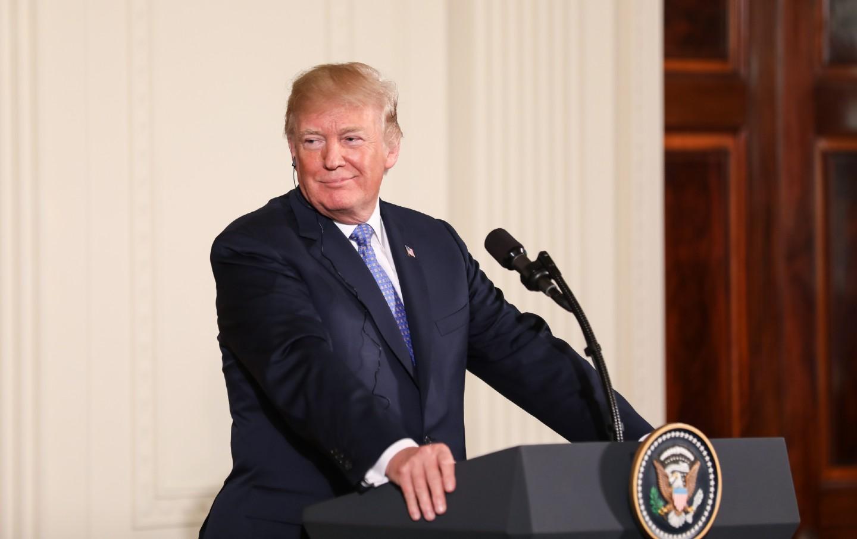 President Donald Trump stands at a podium